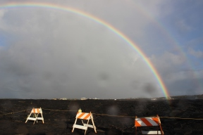 Beautiful rainbow over the lava field and houses.