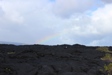 Walking toward the end of Chain of Craters Road. The start of a rainbow over the lava field.