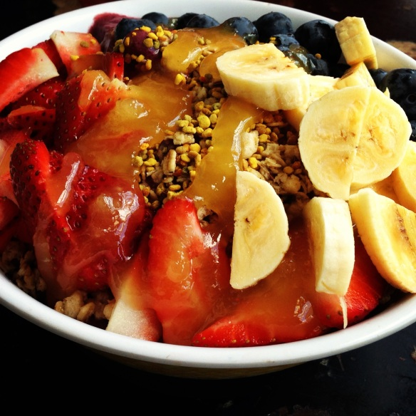 Double acai topped with organic granola, blueberries, strawberries, banana, bee polin and honey
