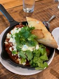 SHASHOUKA housemade merguez + harissa tomato sauce + soft eggs + feta + cilantro + baguette
