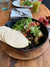 Huevos Rancheros Verde: cumin black beans, two eggs, salsa verde, lime crema, queso fresco, with corn tortillas, and cilantro