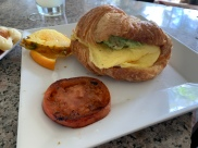 Breakfast Sandwich: Scrambled local eggs, cheddar cheese, grilled tomato, homemade croissant